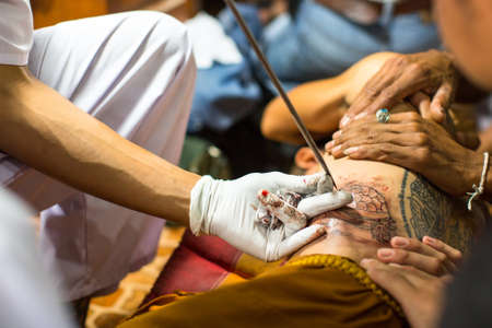 tattooing: WAT BANG PHRA, THAILAND - MAR 18, 2016: Unidentified monk makes traditional Yantra tattooing during Wai Kroo Master Day Ceremony in Bang Pra monastery, about 50 km west of Bangkok.