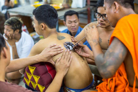 yantra: WAT BANG PHRA, THAILAND - MAR 18, 2016: Unidentified monk makes traditional Yantra tattooing during Wai Kroo Master Day Ceremony in Bang Pra monastery, about 50 km west of Bangkok.