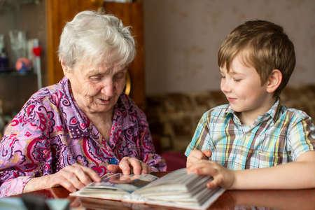Grandmother and grandson looking photo album. Stockfoto