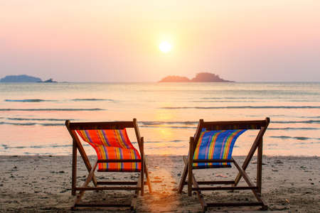 lounge chairs: Two lounge chairs on sunset beach. Stock Photo
