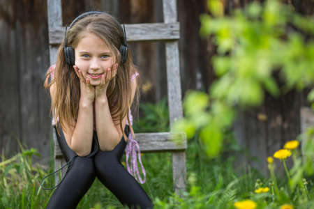 girlie: Cute girlie enjoys music with headphones on sitting in the courtyard of a village house. Stock Photo