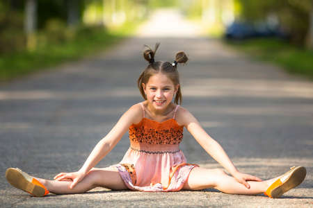 Cheerful little girl sits in the middle of the road.