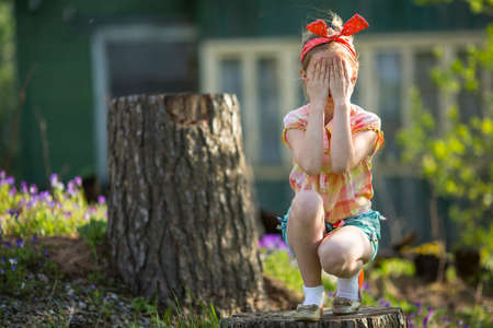 Cute little girl covering her eyes with her hands. See Nothing, Hear Nothing, Say Nothing To Anyone - a series of three photos. Imagens