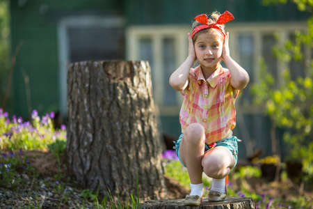 Little cute girl covering her ears with her hands. See Nothing, Hear Nothing, Say Nothing To Anyone - a series of three photos. Imagens