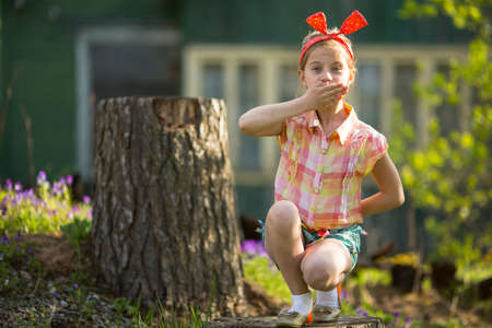 Cute little girl covering her mouth with his hand. See Nothing, Hear Nothing, Say Nothing To Anyone - a series of three photos. Imagens
