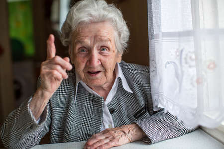 specifies: An elderly woman sitting at a table and specifies the finger. Stock Photo