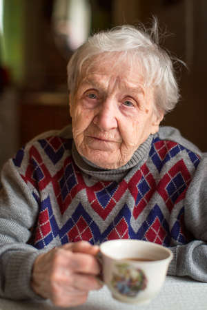 woman drinking tea: Old woman drinking tea.
