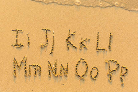 Alphabet written by hand on sandy beach (letters from I to P) Stok Fotoğraf