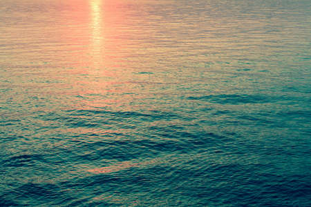 reflection in water: Reflection of the sunset in the emerald sea water. Stock Photo