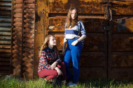 barn girls: Two beautiful teenage girls on the background of an old barn in the woods.
