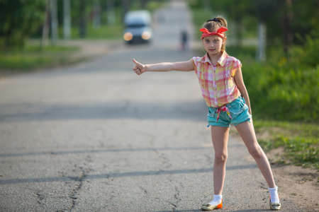 hitchhiking: Little girl hitchhiking along a road. Stock Photo