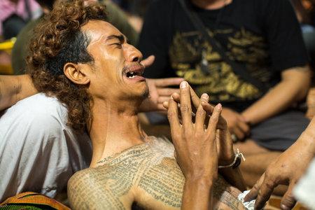 possession: WAT BANG PHRA, THAILAND - MAR 18, 2016: Unknown participants of Master Day Ceremony at able Khong Khuen (spirit possession) during the Wai Kroo ritual at Bang Pra monastery, about 50 km of Bangkok.