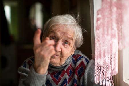 Une femme âgée menace avec un doigt en regardant la caméra.