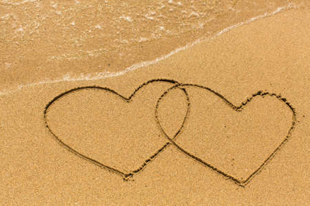evoking: Two hearts drawn on the sand of a sea beach. Stock Photo