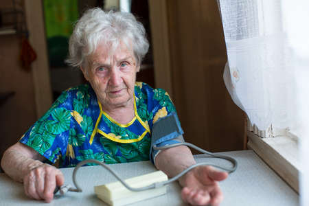 own blood: An old woman measures to itself blood pressure. Stock Photo