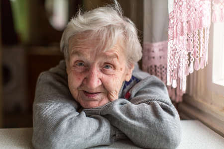 Portrait of an elderly woman, close-up, sitting at the table.
