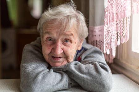 Retrato de una anciana, primer plano, sentado en la mesa. Foto de archivo