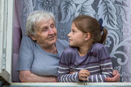 Großmutter mit Enkelin im Fenster sitzen.