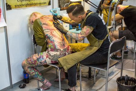 KRAKAU, POLEN - JUNI 11, 2016: De niet geïdentificeerde festivaldeelnemer maakt tatoegeringen bij de 11de Internationale Tatoegeringsovereenkomst in het congres-EXPO Centrum van Krakau.
