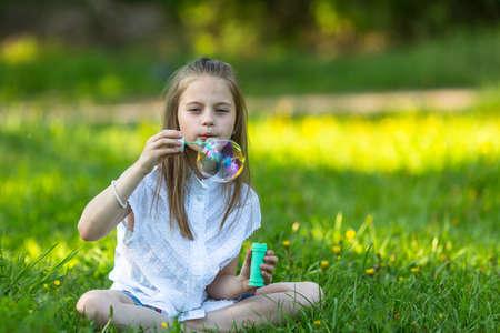 blowing bubbles: Little girl in Park blowing bubbles.