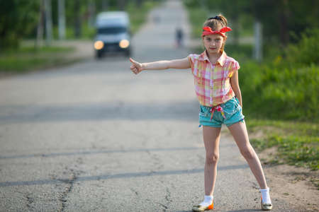 Little funny girl hitchhiker standing on the road. Stock Photo