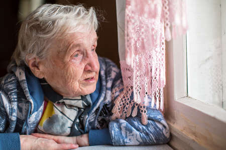 sad lady: An elderly woman near the window.