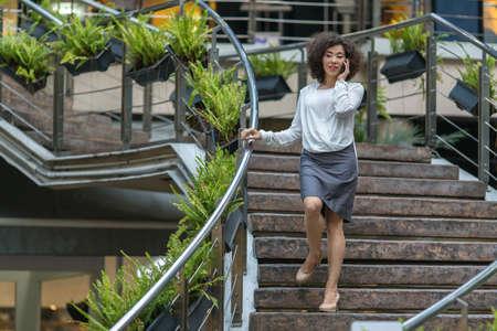hermosa mujer asiática joven hablando por el móvil se ponga sobre los escalones.