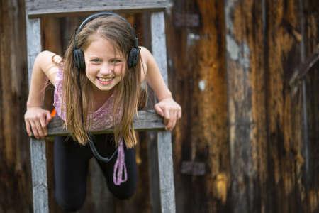 naughty girl: Little naughty girl with headphones outdoors. Stock Photo