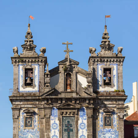 proto: PORTO, PORTUGAL - JUL 12, 2016: Facade of Church of Saint Ildefonso. Completed in 1739, church was built in a proto-Baroque style and features a retable by Italian artist Nicolau Nasoni and a facade of azulejo tilework. Editorial