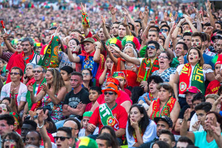 occurrence: PORTO, PORTUGAL - JUL 10, 2016: Portuguese fans during translation of the football match Portugal - France final of the European championship 2016, in Liberdade Square at city center of Porto. Editorial