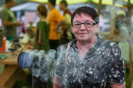 Portrait of a woman at the folk fair near a Smoking samovar.