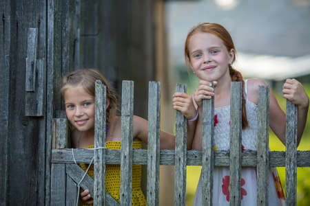 cute girlfriends: Two little cute girlfriends look out for wooden village fence. Stock Photo