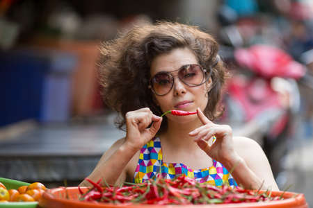 Asian woman with little pepper in the hands portrait in the market.