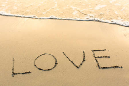 evoking: Love - written manually on the texture of sea sand.