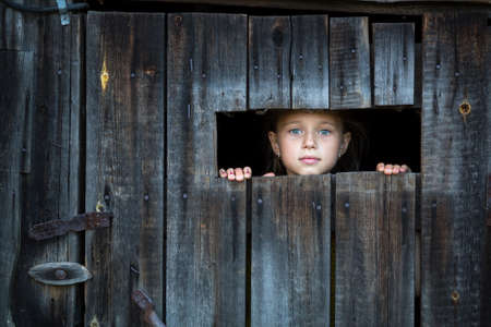 locked in: Little girl peeking through from the window at doors. Locked in the shed.