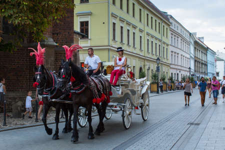 8 year old: KRAKOW, POLAND - SEP 4, 2016: Old-styled carriage for tourists in the streets of Old Krakow. Krakow is visited by over 8 million tourists a year, number of foreign tourists up to 2 million people.