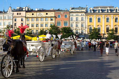 coachman: KRAKOW, POLAND - SEP 8, 2016: Old-styled carriage for tourists in the streets of Old Krakow. Krakow is visited by over 8 million tourists a year, number of foreign tourists up to 2 million people.