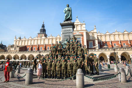 mickiewicz: KRAKOW, POLAND - FEB 11, 2016: Polish soldiers in the free day posing at the camera near Adam Mickiewicz Monument at the Main Market Square, the Cloth Hall in the background. Editorial