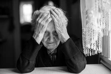 An elderly woman sitting at the table in a depressed state, black and white photo.