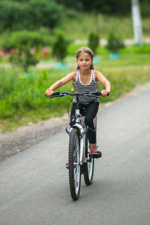 petite girl: Petite girl rides a mountain bike. Stock Photo