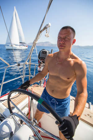 yachtsman: Yachtsman skipper during race, on his sailing yaht boat on the sea. Stock Photo