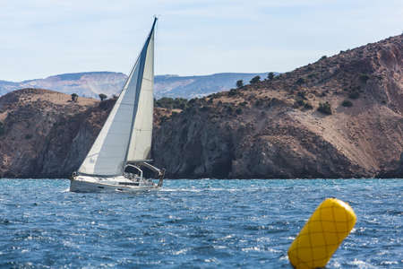 ship bow: Sailing yacht in the finish during the race regattas near the coastal cliffs in the Aegean sea.
