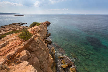 encompasses: Rocky promontory in the Aegean sea near Athens. Stock Photo