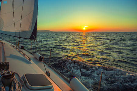 Sailing in the wind through the waves during sunset at the Aegean Sea in Greece. Luxury yachts. Stock Photo