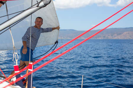 Young man skipper - setting sails on the sailing yacht boat. Vacation, holidays, travel.