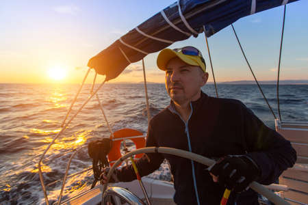 steers: Captain steers the sailing yacht on the sea during sunset. Stock Photo