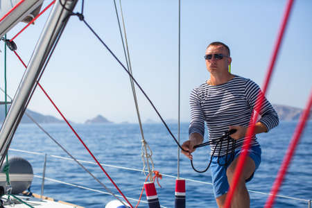 Young man skipper at his sail boat, controls ship during sea yacht race. Luxery vacations, sailing, adventure, travel.