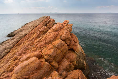 encompasses: Rocky shore by minerals of the red color, the Aegean sea, near Athens, Greece.