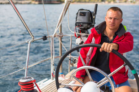 route master: Skipper at the helm controls of a sailing yacht.