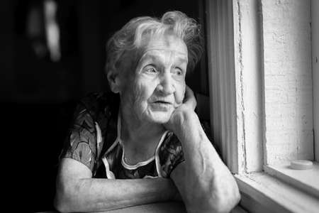 An elderly woman sitting near the window. Black-and-white photo.
